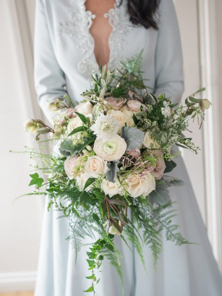 Bride holding loose floral bouquet of creams, ferns anemones and blush rustic flowers.