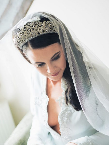 Portrait of Bride in wedding crown and veil in custom designed low cut wedding dress