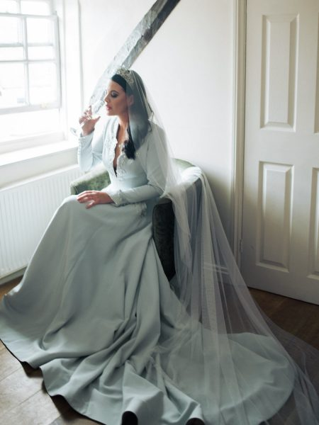 Portrait of Bride sipping champagne in front of window wearing soft blue green duck egg wedding skirt and top and modern wedding crown
