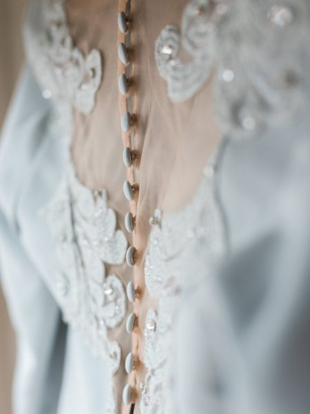 Close up detail of buttons, sheer fabric and embroidery embellishment of Bride's soft duck egg blue wedding dress