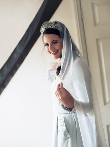 Portrait of Bride smiling holding side of veil wearing soft blue green duck egg wedding skirt and top and modern wedding crown