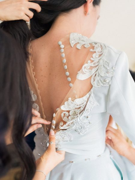 Close up of back of Bride as her top is buttoned up by Bridesmaid showing off detail of buttons, sheer fabric and embroidery embellishment of Bride's soft duck egg blue wedding dress