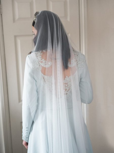 Back view of Bride in her soft duck egg blue wedding dress and delicate veil