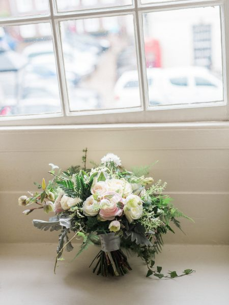 Loose floral bouquet of creams, ferns, ranunculus, anemones and blush rustic flowers.