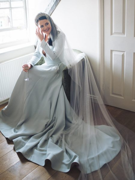 Portrait of Bride smiling in front of window wearing soft blue green duck egg wedding skirt and top and modern wedding crown