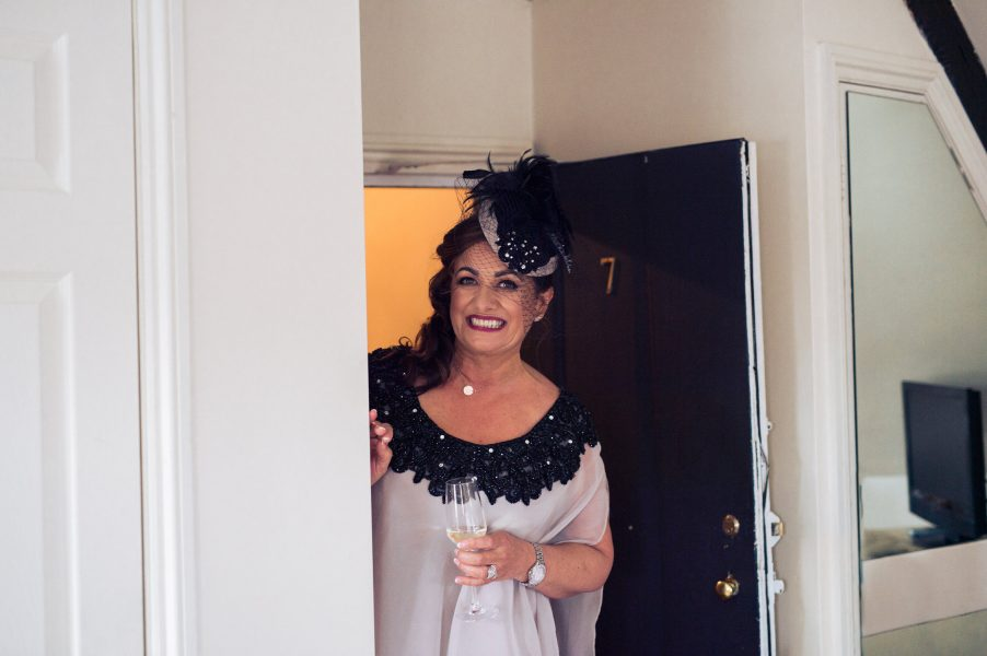 Mother of Bride in Black fascinator holding glass of champagne smiling as she looks at Bride
