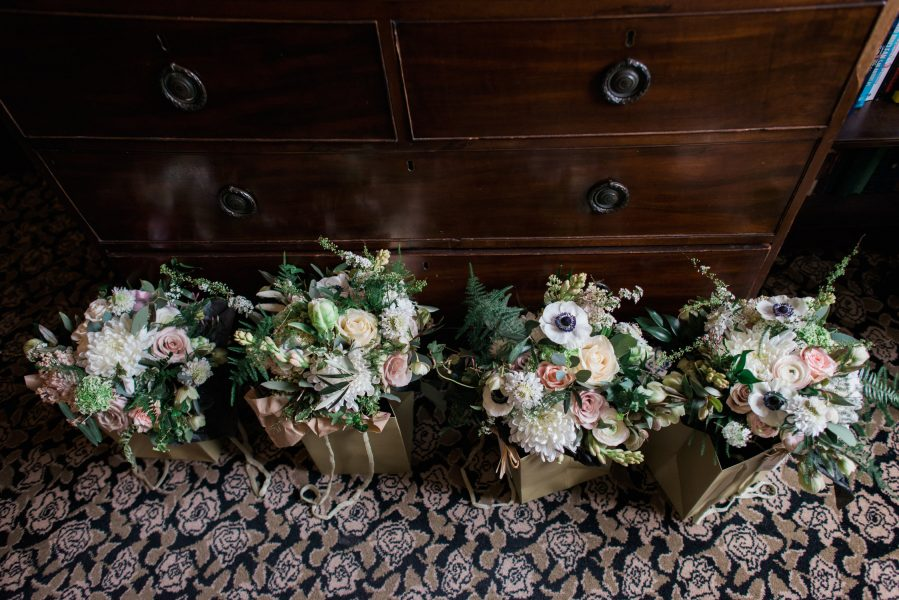 Line up of wedding flowers consisting of loose floral bouquet of creams, ferns, ranunculus, anemones and blush rustic flowers.
