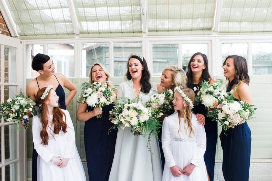 Bride and maids relaxed portrait laughing holding loose rustic bouquets of flowers in conservatory