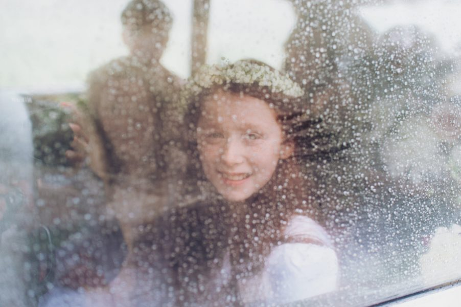 Flower girl smiling as she peers out of wedding car window covered in raindrops