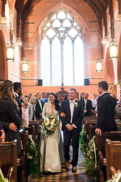 Bride walks down aisle with father in St Johns Baptist Church Shedfield
