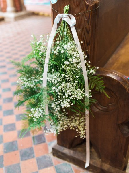 Rustic ferns and gypsophila decorate a chuch pew at St Johns Baptist Church Shedfield