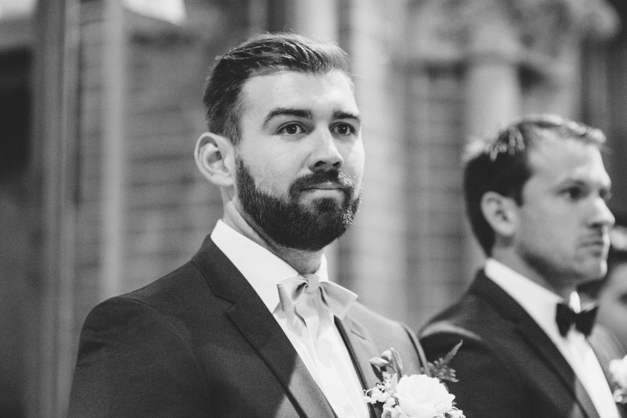 Black and white portrait of Groom's face as he watches Bride walk down aisle at St Johns Baptist Church Shedfield