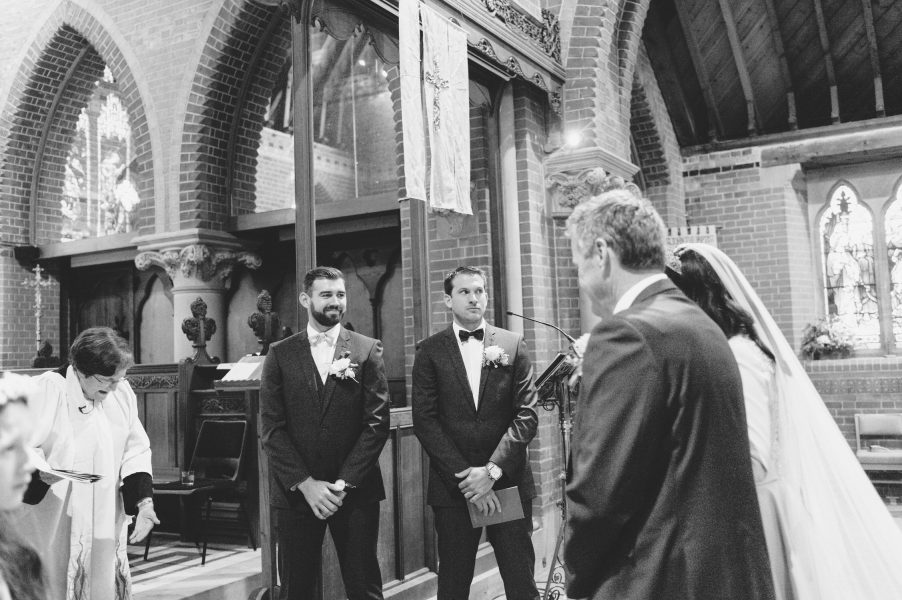Black and white portrait of Groom and Best Man as Bride and Father of Bride walk down aisle at St Johns Baptist Church Shedfield