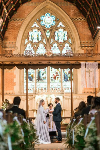 Bride and Groom take vows with stained glass window backdrop at St Johns Baptist Church Shedfield