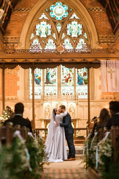 Bride and Groom's first kiss with stained glass window backdrop at St Johns Baptist Church Shedfield