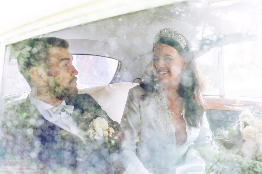 Bride and Groom enjoy a happy moment chatting in back of Rolls Royce wedding car behind a window covered in raindrops St Johns Baptist Church Shedfield
