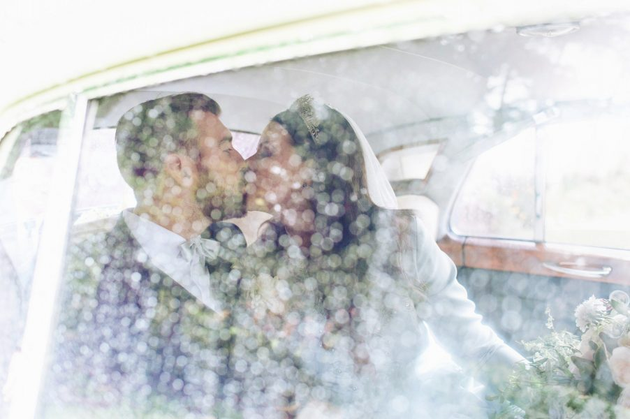 Bride and Groom kiss in back of Rolls Royce wedding car behind a window covered in raindrops St Johns Baptist Church Shedfield