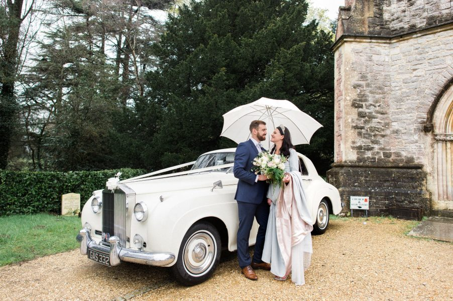 Bride and Groom stand under umbrella in front of Rolls Royce wedding St Johns Baptist Church Shedfield