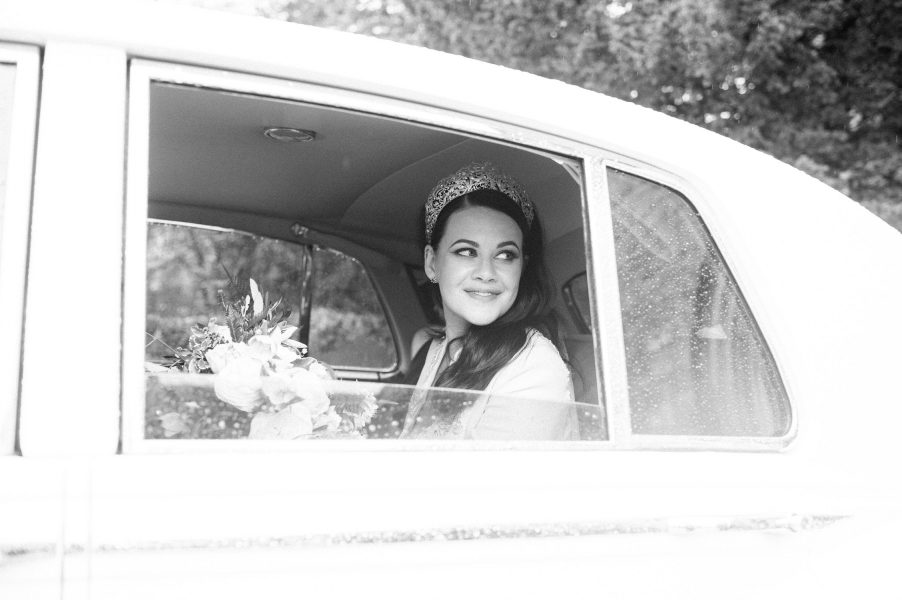 Bride gazing out of half wound down car window covered in raindrops
