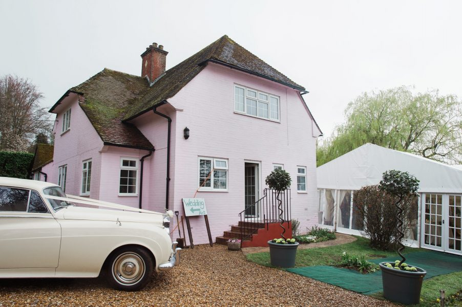 Pink cottage with wedding Rolls Royce outside and marquee in background Hampshire