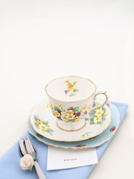 Vintage Teacup with purple and yellow pansy sitting on blue napkin in marquee Hampshire