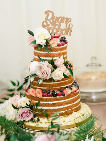 Naked cake decorated in flowers and Bride and Groom cake topper in gold glitter
