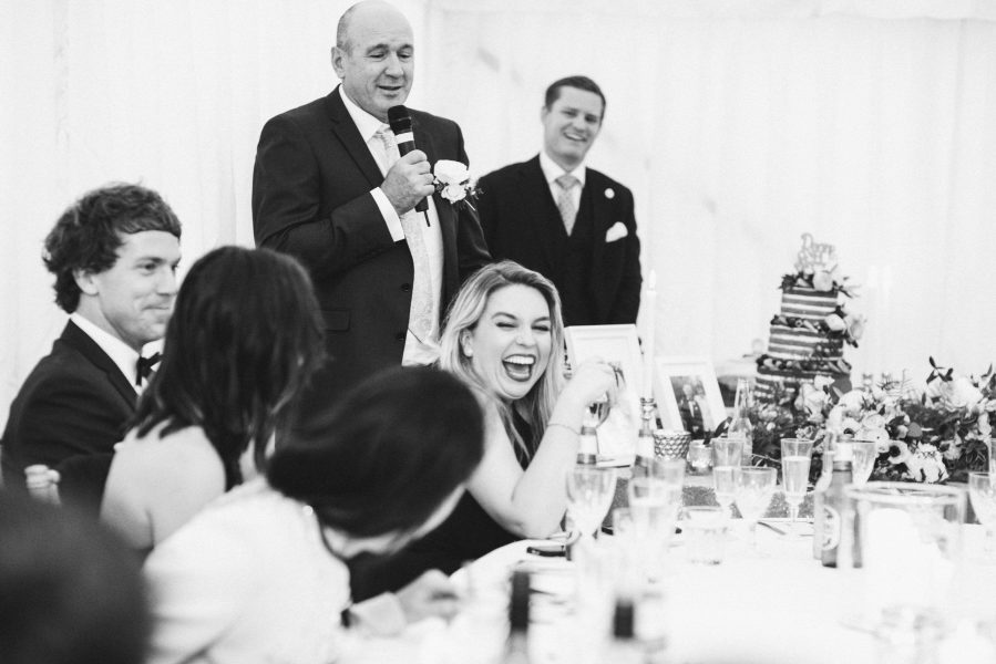 Bridesmaid laughing at the wedding speeches in marquee