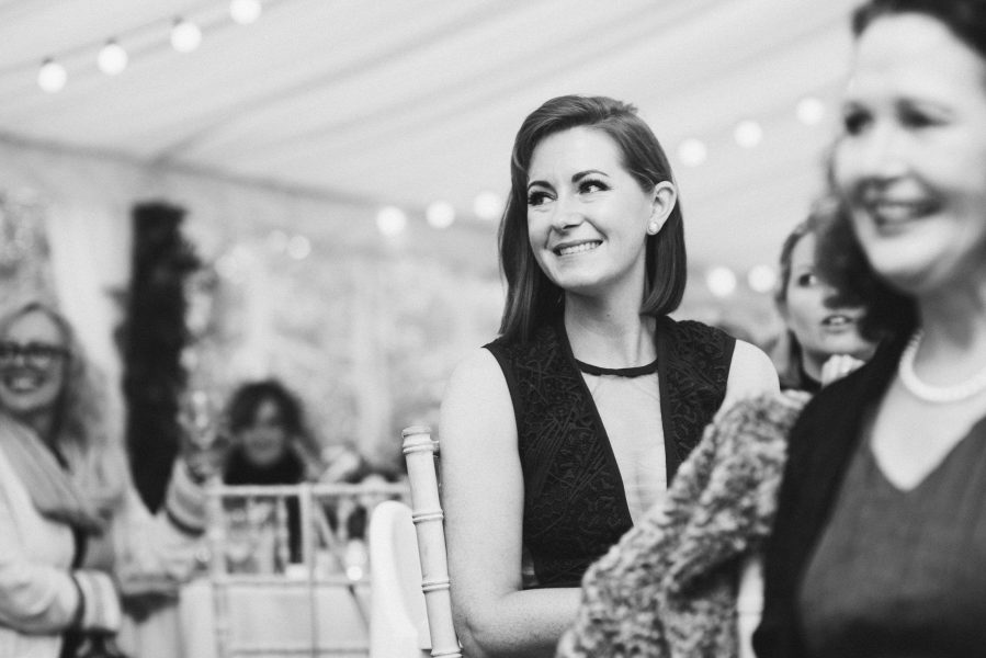 Wedding guest smiling during wedding speeches in marquee