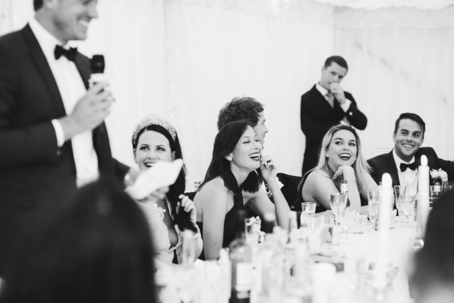 Bridal party laugh at wedding speeches