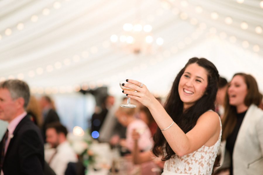 Guest raises vintage champagne glass in wedding marquee