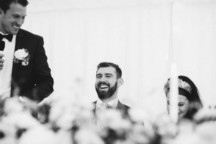 Grooms laughing at wedding speech