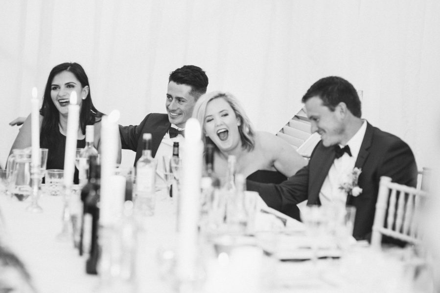 Bridesmaids and Bridal party laughing at wedding speech