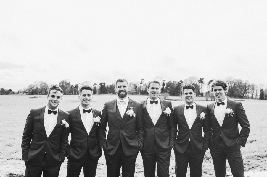 Black and white wedding portrait of Groom's party smiling in Hampshire field