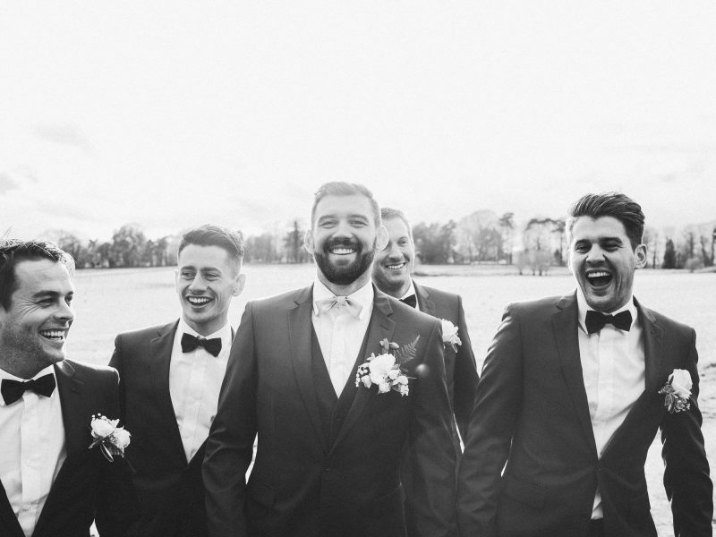 Black and white wedding portrait of Groom's laughing as they walk towards camera in Hampshire field