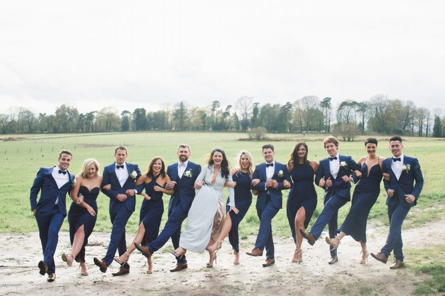 Wedding portrait of whole stylish Bridal party having fun kicking legs armed linked in Hampshire field