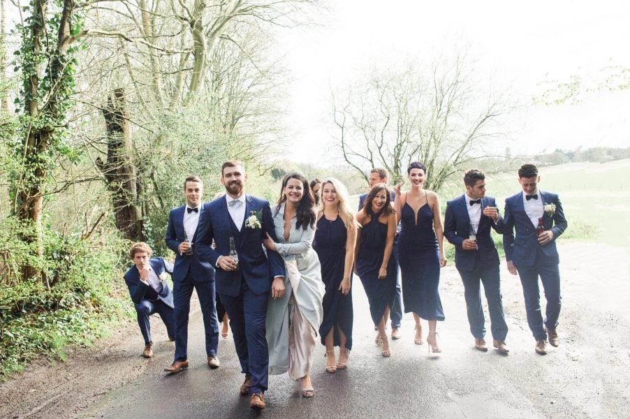 Candid moment of stylish wedding party walking up country lane Hampshire