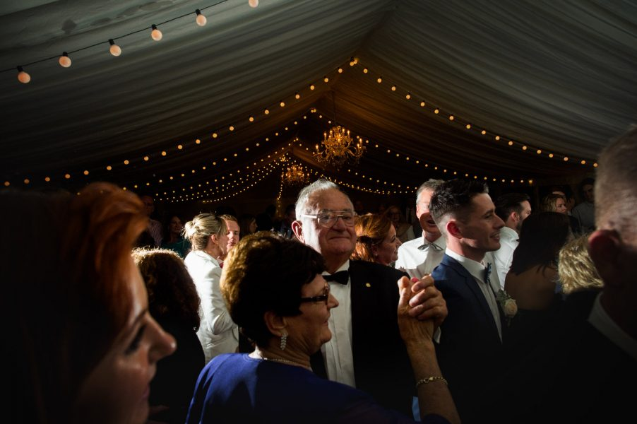 Guests dance on wedding dance floor in marquee