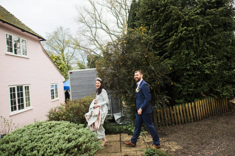 Bride and Groom walk towards pink cottage Hampshire