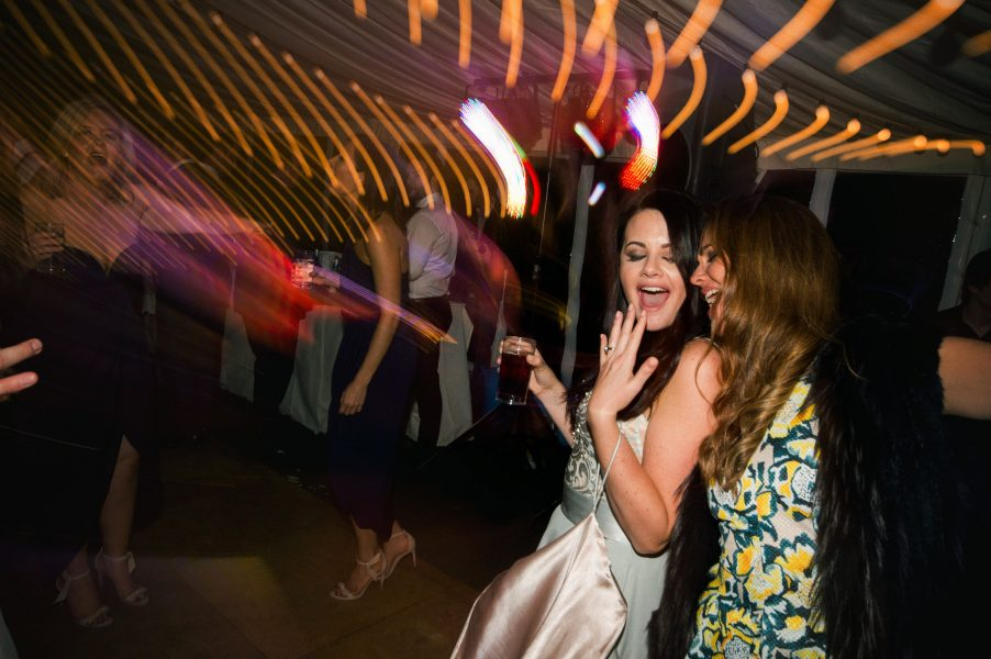 Bride dances on wedding dance floor with swirling light trails surrounding her