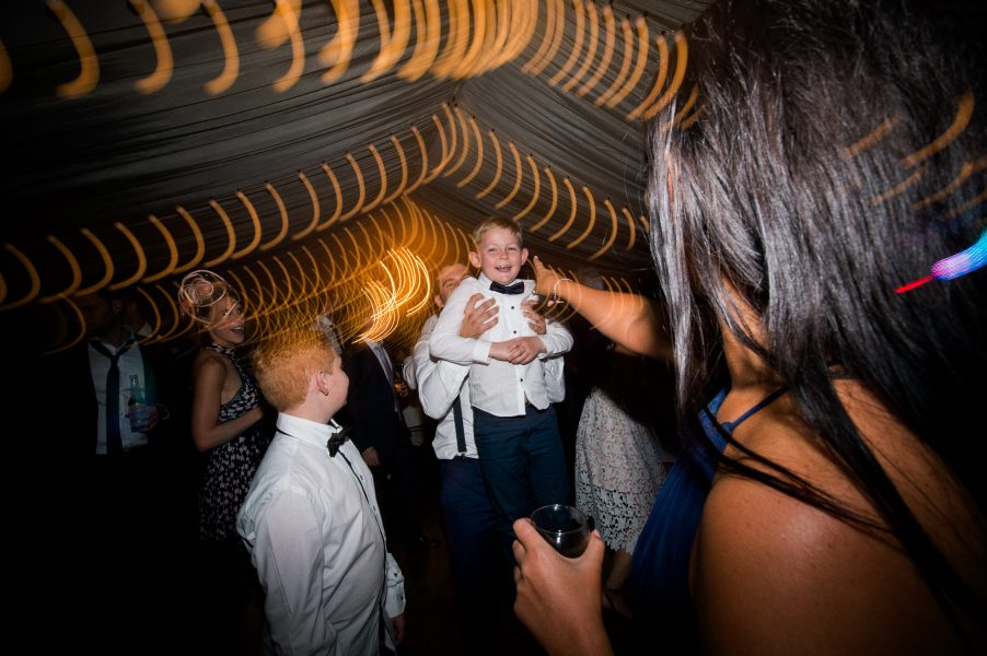 Small boy being listed in air having fun on wedding dance floor with orange swirling light trails