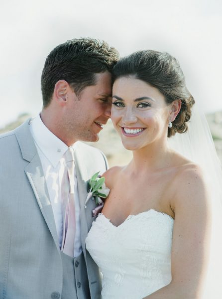 Fine art portrait of Bride smiling at camera while Groom rests his head affectionately against Bride