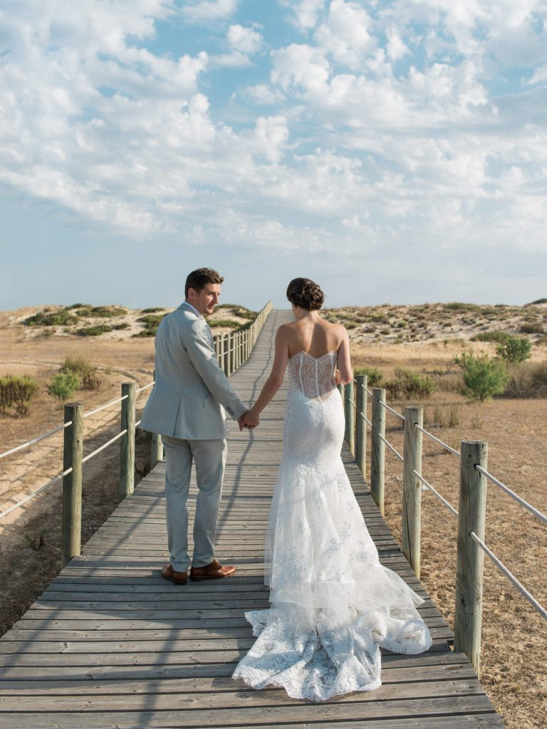 Fine art portrait of Bride and Groom walking along a wooden walkway over sand and nature reserve showing off back of Brides dress and dramatic clouds