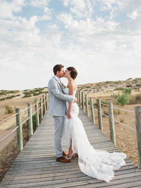 Fine art portrait of Bride and Groom kissing with a dramatic clouds backdrop Quinta Do Lago