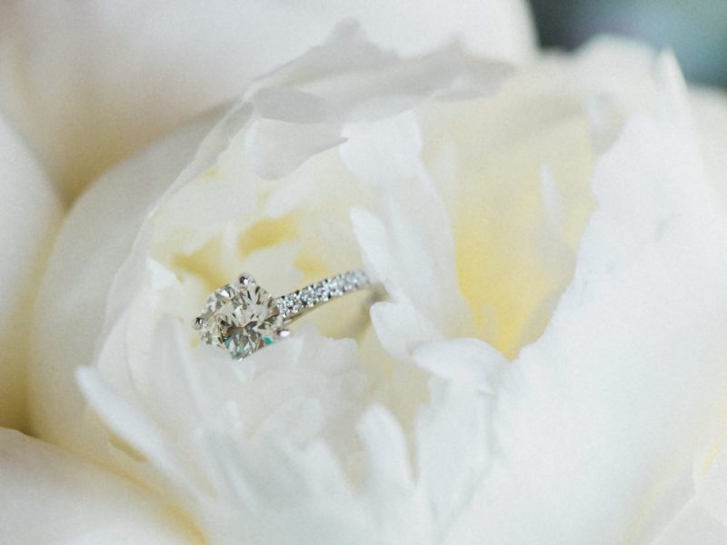 Close up of engagement ring in cream peony flower
