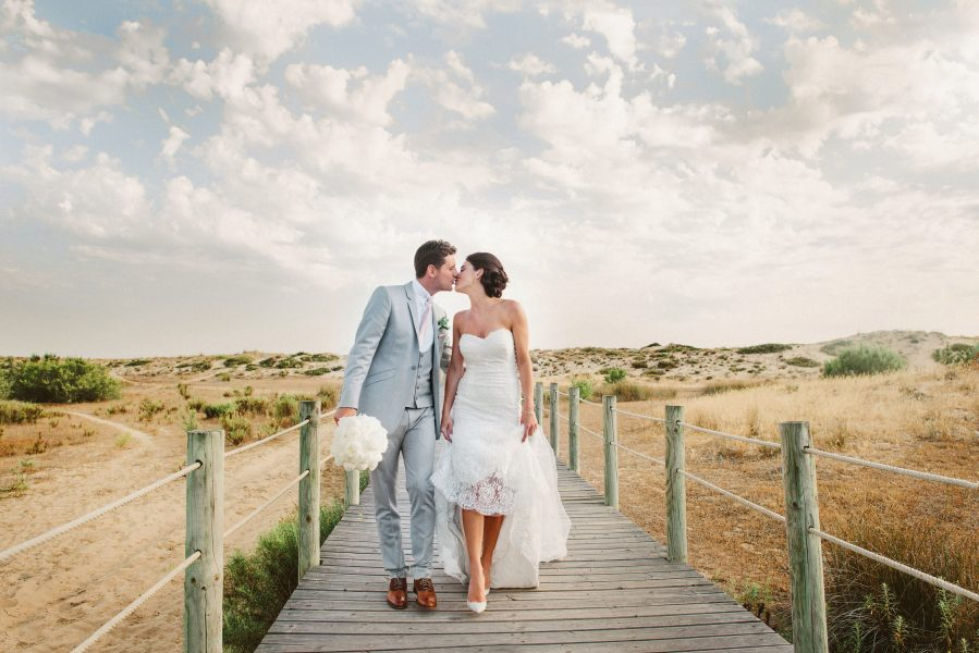 Fine art portrait of Bride and Groom kissing as they walk towards camera with a dramatic backdrop of clouds and coastal beauty Quinta Do Lago