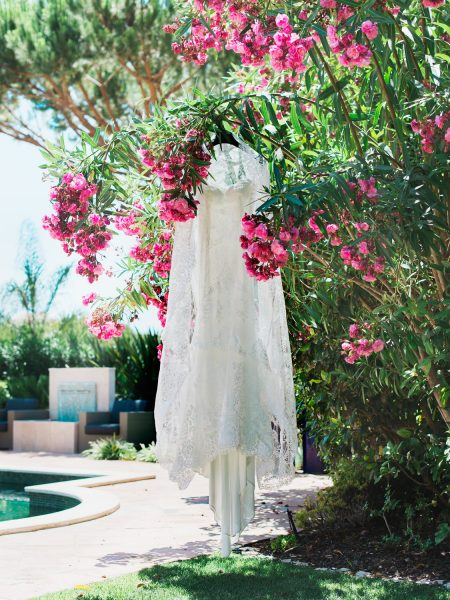Lace dress hanging next to swimming pool and pink flower Algarve Portugal