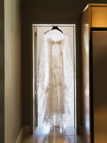 Delicate lace dress hanging in doorway with light streaming through Algarve Portugal