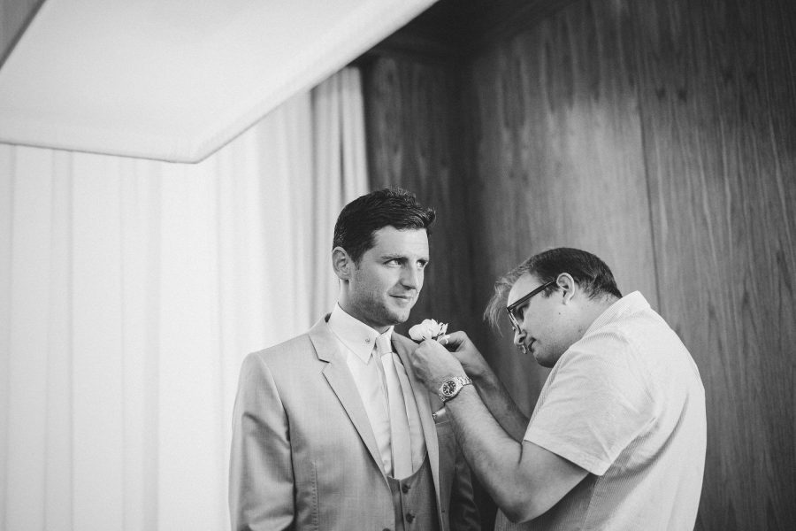 Groom having button hole pinned by stylist in Algarve Portugal