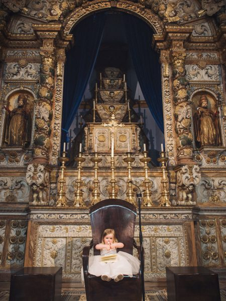 Flower girl sits in church chair giving the thumbs up surrounded by orate church decorative detailing in Loule Algarve Portugal
