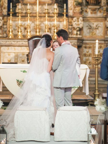 Back view of Bride and Groom with ornate gold church detailing Loule Algarve Portugal
